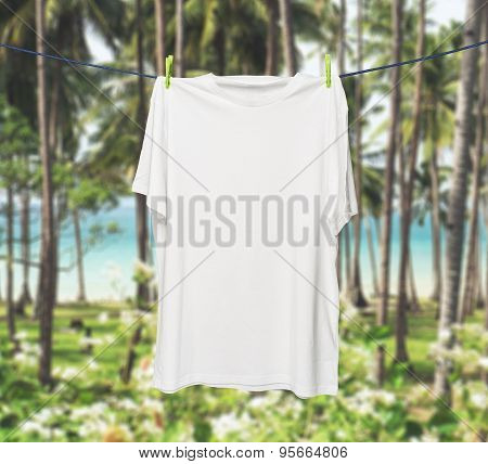 Close Up Of A White T-shirt On The Rope. Tropical Jungles And Sea In A Blur As A Background.