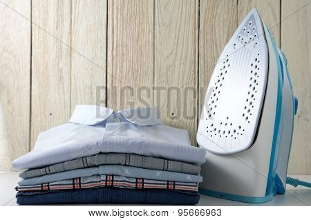 Clothes And Iron With Wood Background