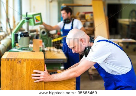 Two Young Worker In A Carpenter's Workshop