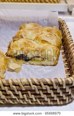 Close Up Of Soft Bread Roll Or Bun With Slice Almond Topping In Basket At Bakery Shop