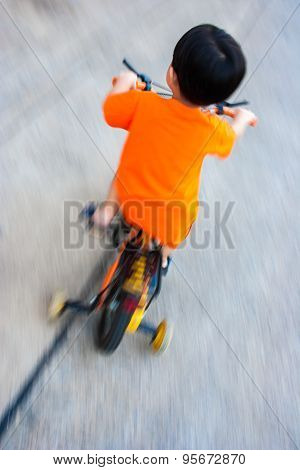 A boy is riding bicycle.