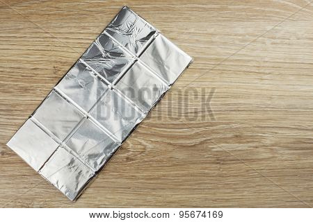 Chocolate wrapped in aluminum foil on a wooden board.