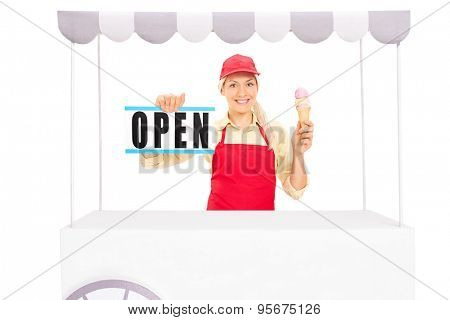 Young female vendor holding an ice cream cone and an open sign behind an ice cream stand isolated on white background