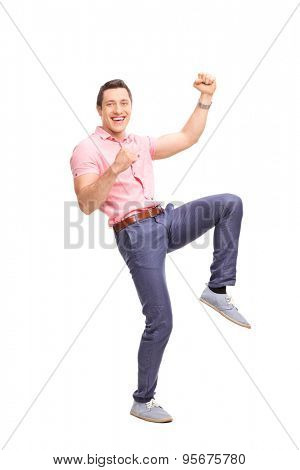 Full length portrait of an excited young guy gesturing happiness and looking at the camera isolated on white background