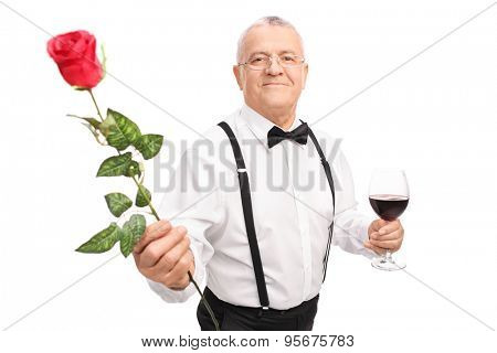 Romantic senior gentleman holding a glass of red wine and handing a red rose towards the camera isolated on white background