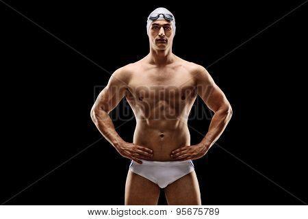 Handsome young male swimmer posing in white swim trunks on black background