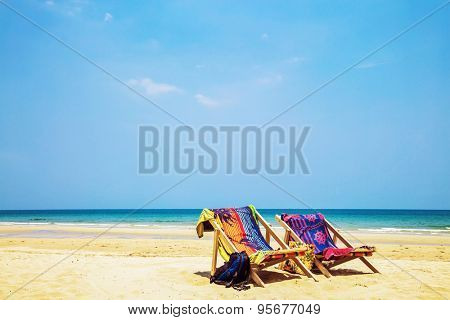sun beach chairs on shore near sea. Thailand