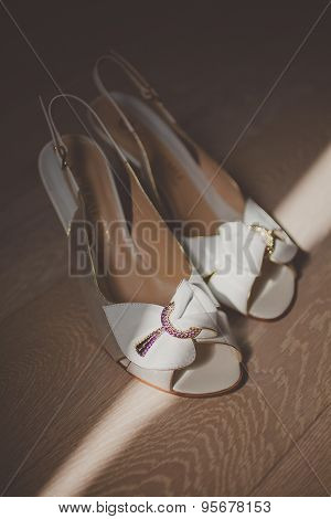 White elegant wedding shoes with bow on a wood background