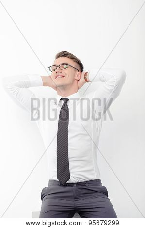 Businessman standing with arms behind head