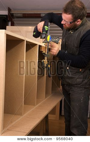 Carpenter Making Cabinet In Workshop