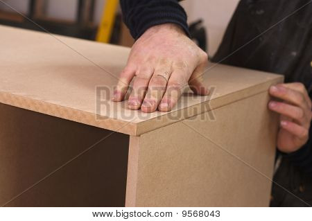 Carpenter Making Cabinet In Workshop