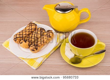 Hot Tea In Cup, Teapot And Eclairs On Table