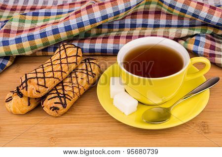 Three Eclairs, Hot Tea In Cup And Sugar On Table