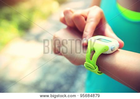 young woman jogger ready to run set and looking at sports smart watch