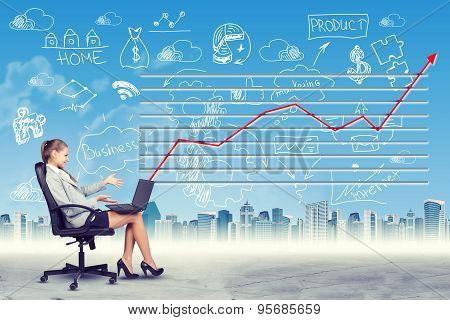 Happy woman sitting in chair working on laptop