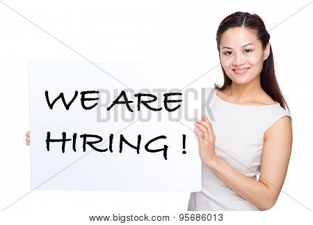 Woman holding with white poster presenting phrase of we are hiring