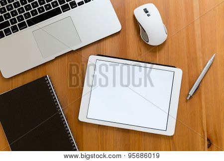 Office table with digital tablet showing a blank screen for advertising