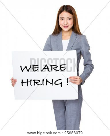 Business woman show with white banner for phrase of we are hiring