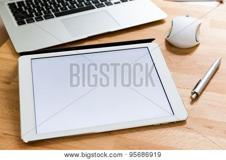 Working desk with mobile phone and digital tablet showing a white screen