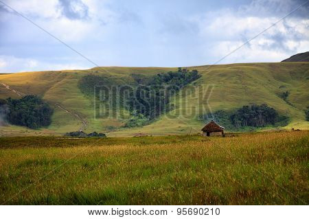 Traditional Round Hut In Savanna With Cloud Raising From The Ground
