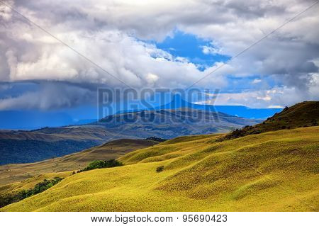 Stunning Landscape - Hills Of Savanna Covered With Yellow Grass Under Stormy Cloudy Sky