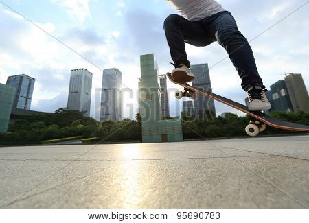young woman skateboarder skateboarding at sunrise city