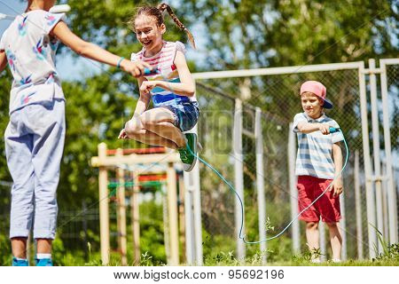 Happy girl jumping over skipping-rope held by her friends outdoors