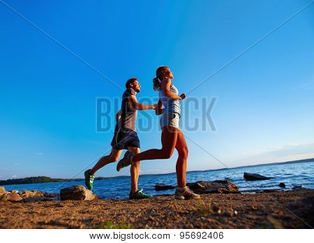 Happy couple running down sea shore