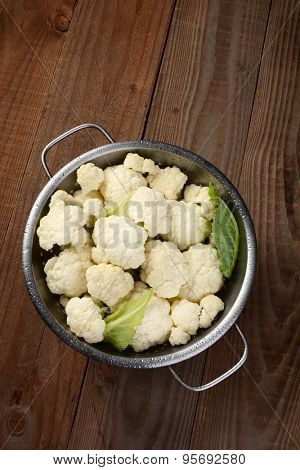 High angle view of a colander filled with cauliflower florets. On a rustic wood table. Vertical format.