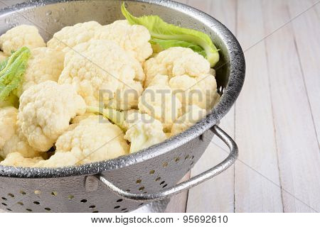 Closeup of a colander full of cauliflower florets. Misted with water on a white wood table.
