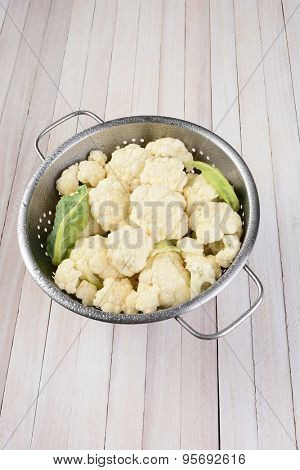 Vertical high angle view of a head of cauliflower in a metal colander on a rustic wood table, with copy space.