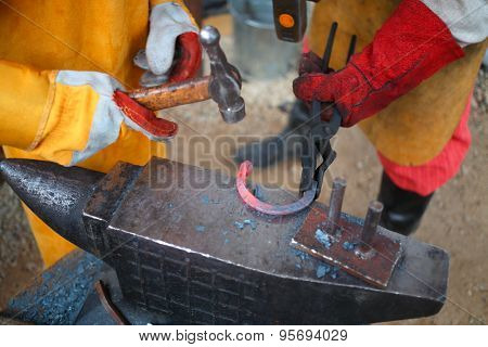 Process of forging iron red-hot horseshoe on anvil billet in smithy