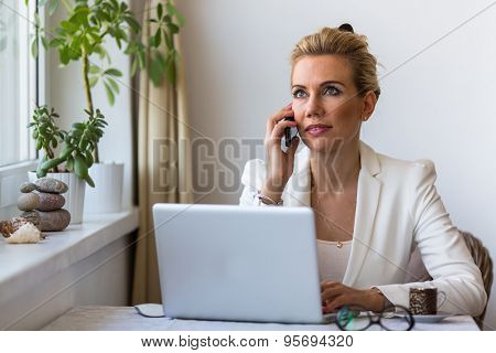 Young business woman with laptop in the office talking on a cell phone. Management and conclusion of transactions.