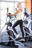 picture of elliptical  - Beautiful young blond girl wearing a white top and grey leggings standing on elliptical trainer near a big window in a fitness club - JPG