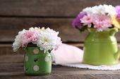 foto of chrysanthemum  - Beautiful chrysanthemums in pitchers on wooden background - JPG