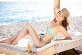 stock photo of sunbathing woman  - Smiling beautiful woman sunbathing in a bikini on a beach at tropical travel resort - JPG