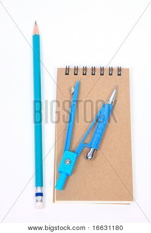 a note pad, compass, pencils and diary on white