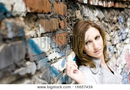 Close-up of an attractive young woman leaning against a graffiti painted wall