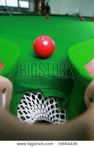red billiard ball  in front of corner pocket on green baize table