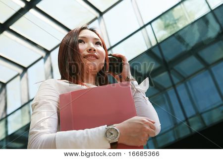 young asian business women holding folder and mobile phone