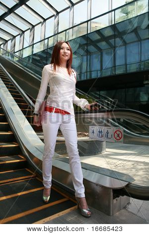 young asian business women holding mobile phone on escalator