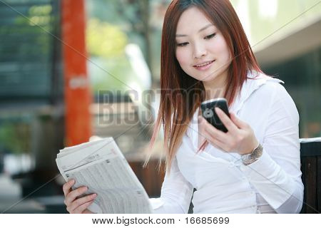 young asian businesswomen reading newspaper and holding mobile phone