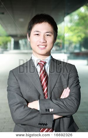 a yong Asiatic businessman  is walking outdoor at night