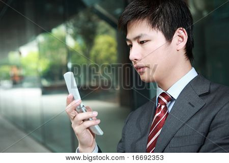 a yong Asiatic businessman  is answering phone outdoor at night