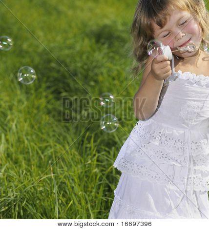 little girl blowing bubbles on green grass