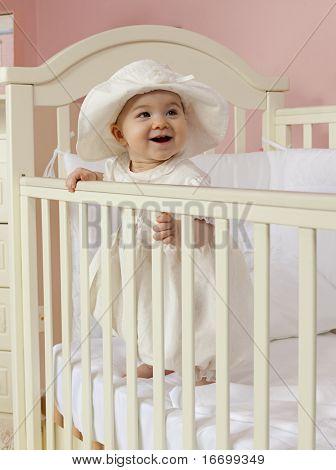 Baby-Mädchen im Bett im Kinderzimmer stehen lächelnd