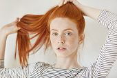 Youth, Tender Age And Lifestyle Concept. Fashionable Young Woman With Freckled Tying Her Beautiful G poster