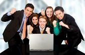 stock photo of business success  - Business success team in an office in front of a laptop computer - JPG