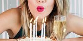Pretty Girl Blowing Out Celebration Candles On Delicious Cake poster