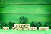 Happy St Patricks Day Wooden Blocks With Shiny Shamrocks Over A Green Wooden Background poster